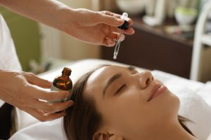 Anti-aging Skin Care. Closeup Of Beautiful Smiling Woman Receiving Essential Oil Therapy